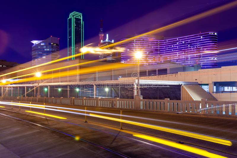 Light trails from moving streetcar on the Houston Street with the city of Dallas in background.  royalty free stock photos