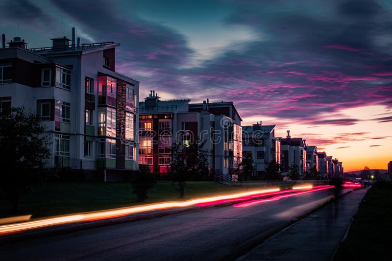 Light trails of passing cars in front of houses during sunset with purple clouds. Light trails of passing cars in front of houses during beautiful sunset with stock photos