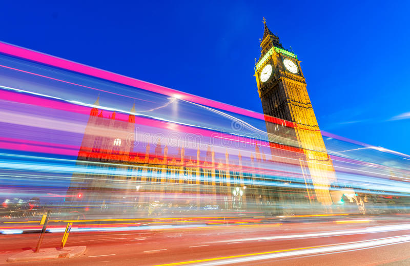 Light trails of Red Bus in front of Big Ben and Westminster Palace.  stock photo