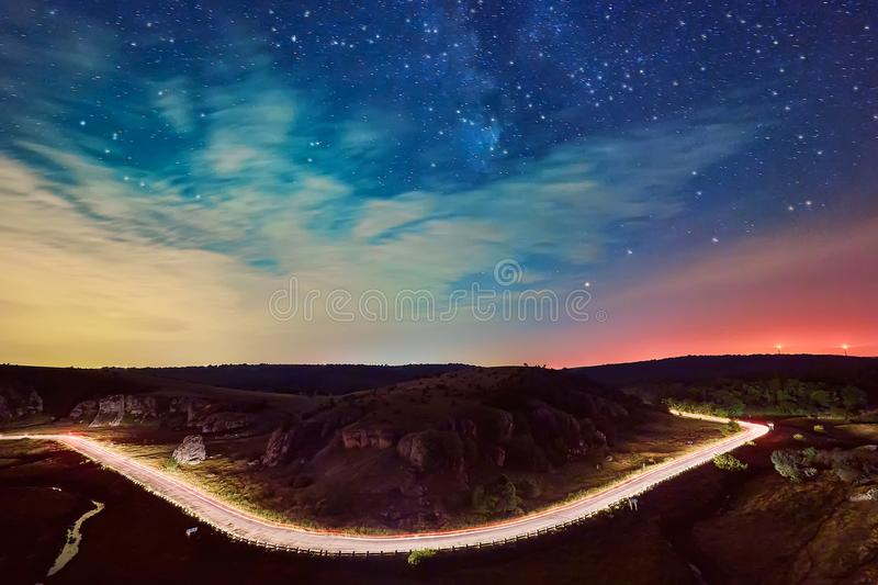 Light trails on the road and a beautiful starry sky over the hills of Dobrogea royalty free stock photo