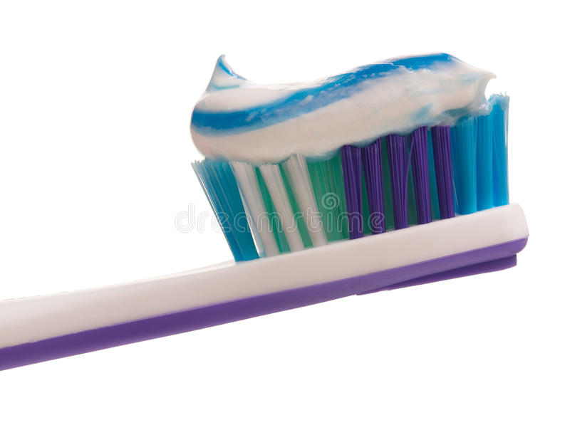 Light-violet toothbrush. With toothpaste isolated on white background stock images