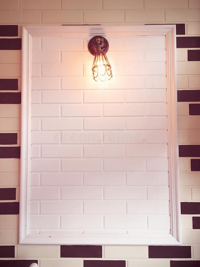 Light on the wall. Lightbulb on a beautiful framed white brick and tiled wall stock photo