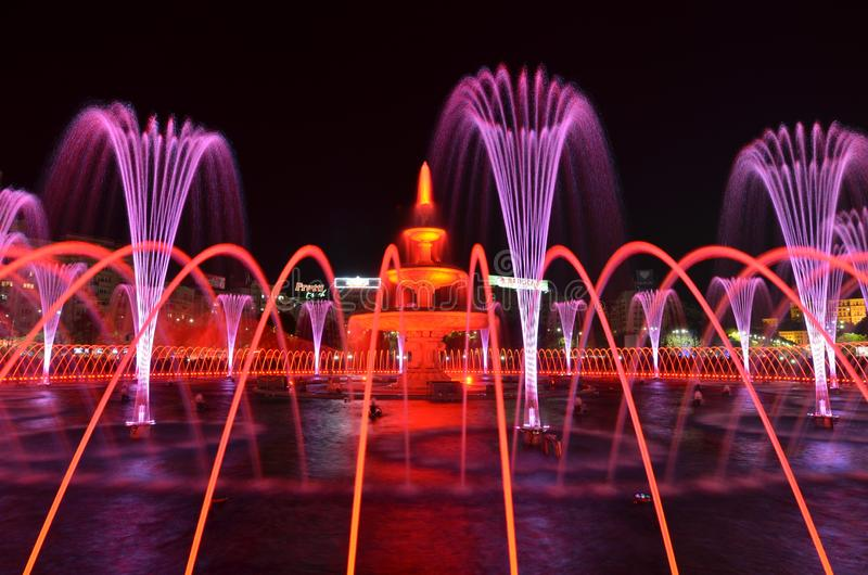 Light and water night show. Pink and red color. Bucharest, Romania - October 7, 2018: Magnificent night show of colorful lights, laser beams, music and water stock photography