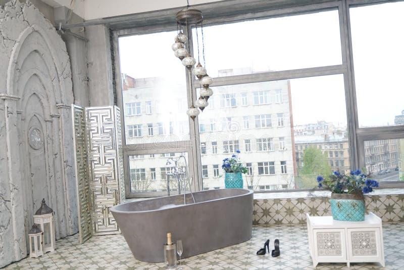 Light white stone bathroom interior with big window view. Beauty grey gray stone bathroom design in big room apartment stock photography