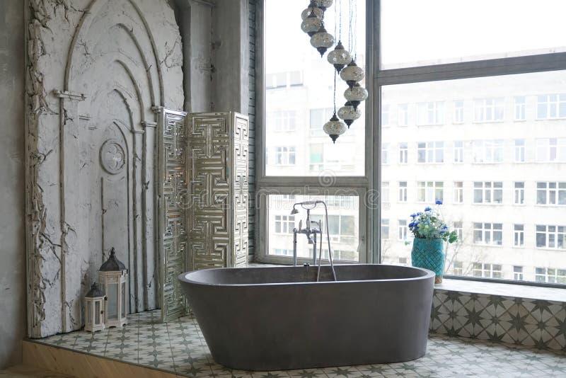 Light white stone bathroom interior with big window view. Beauty grey gray stone bathroom design in big room apartment royalty free stock image