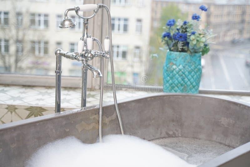 Light white stone bathroom interior with big window view. Beauty grey gray stone bathroom design in big room apartment stock image