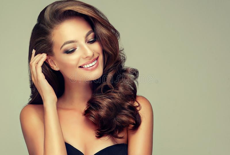 Light and wide smile on the face of young, brown haired beautiful model with long, curly, well groomed hair. Excellent hair wav stock image