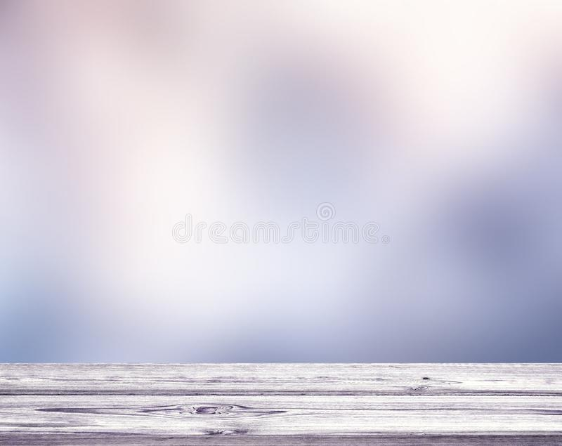 Light wooden empty table texture. Winter violet frozen sky blurred background. royalty free stock photography