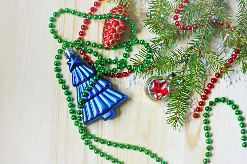 On a light wooden surface is a branch of spruce, garland and Christmas decorations. royalty free stock images
