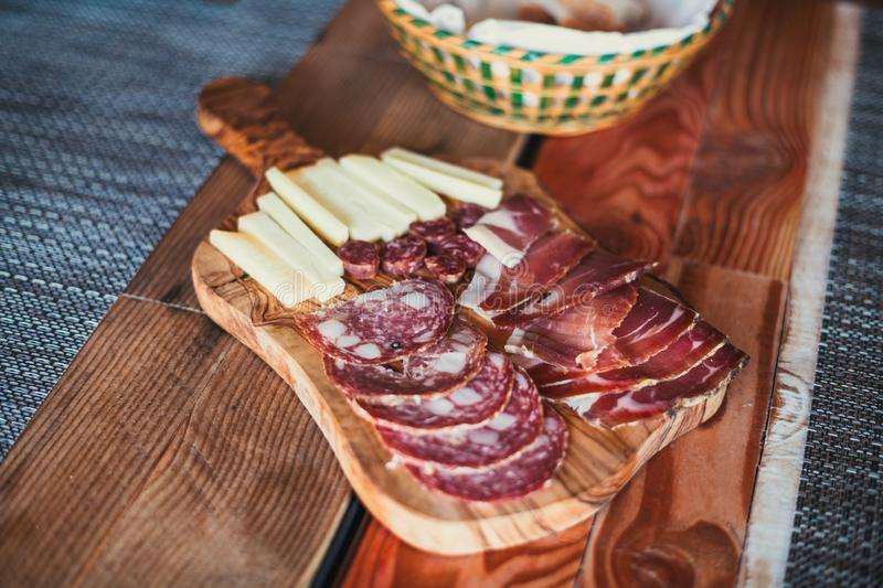Light wooden table setting: white plates, rustic dark table cloth with salami, cheese, vine, and ham. Top view.  stock images