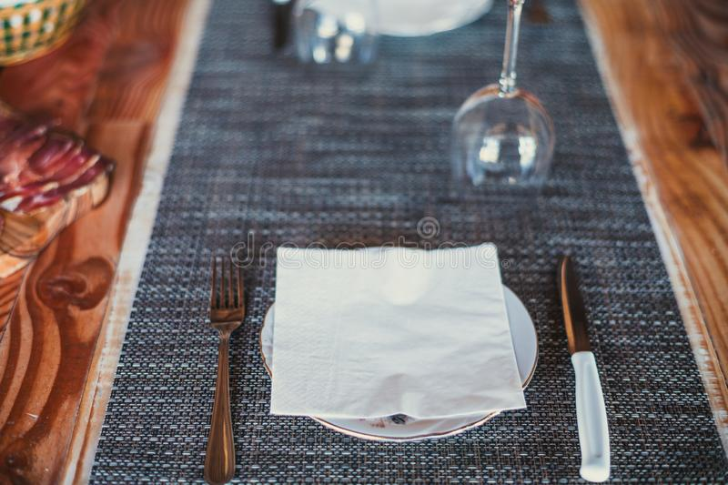 Light wooden table setting: white plates, rustic dark table cloth with salami, cheese, vine, and ham. Top view.  stock photography