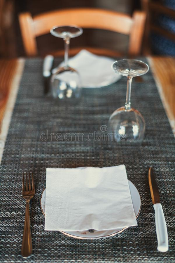 Light wooden table setting: white plates, rustic dark table cloth with salami, cheese, vine, and ham. Top view.  stock photos