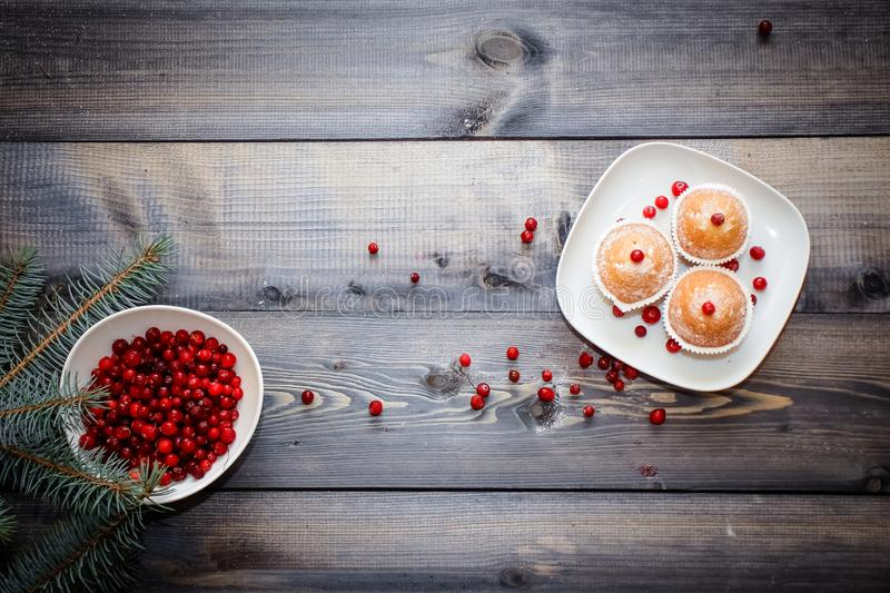 A light wooden table top with a plate of freshly baked muffins decorated with red berries sprinkled with white powder and a plate stock photos