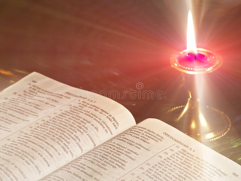 Light in the world. Open Bible in candlelight