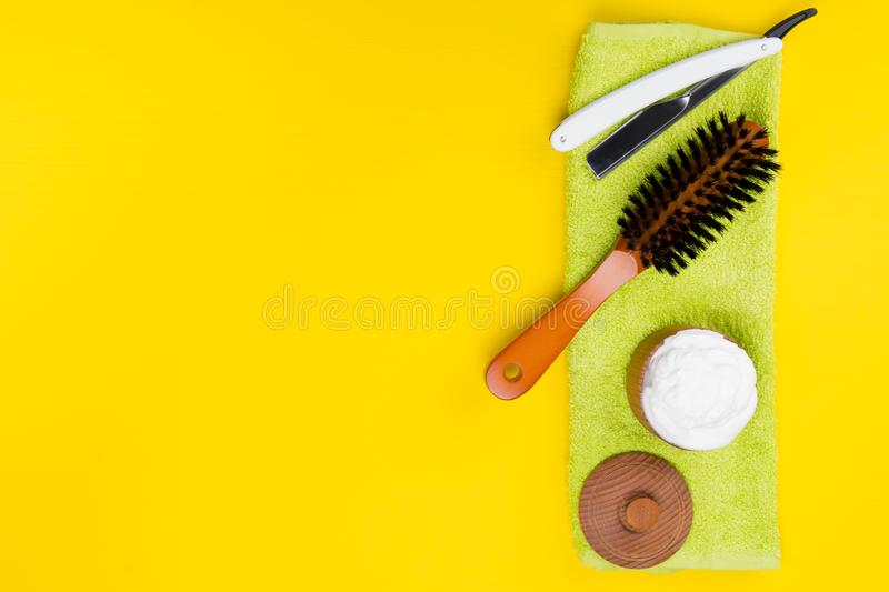 On a light yellow background, lie objects to create. beautiful beards, scissors, shaving foam and brush. stock image