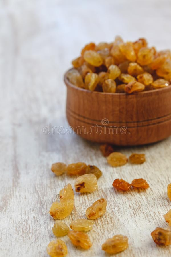 Light yellow raisins in a wooden bowl on a light white background. Close-up. Isolated.  stock photos