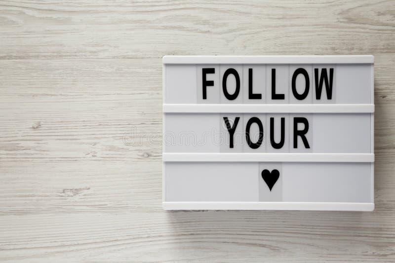 Lightbox com texto 'segue-o coração 'sobre a superfície de madeira branca Copie o espaço foto de stock