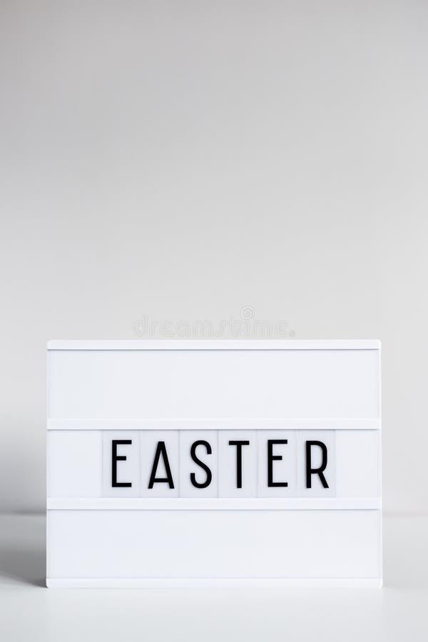 Lightbox d'annata con la parola Pasqua sullo spazio della copia e della tavola sopra la parete fotografia stock
