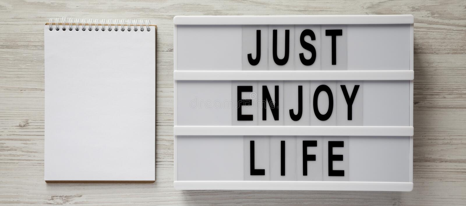 A lightbox with `Just enjoy life` words, blank notepad on a white wooden surface, top view. Copy space stock photography