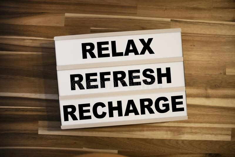 Lightbox or light box with message Reflex Refresh Recharge on a wooden table. Lightbox or light box with message Reflex Refresh Recharge royalty free stock images