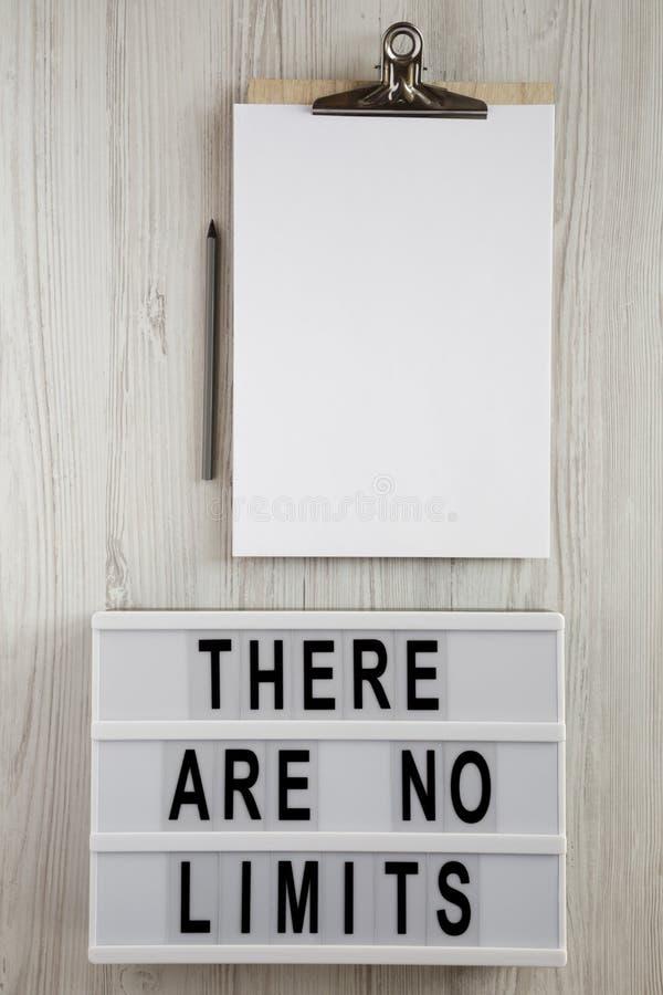 Lightbox mit Text 'dort sind keine Grenzen ', Klemmbrett mit Blatt Papier und Bleistift auf einem weißen hölzernen Hintergrund, D stockbild