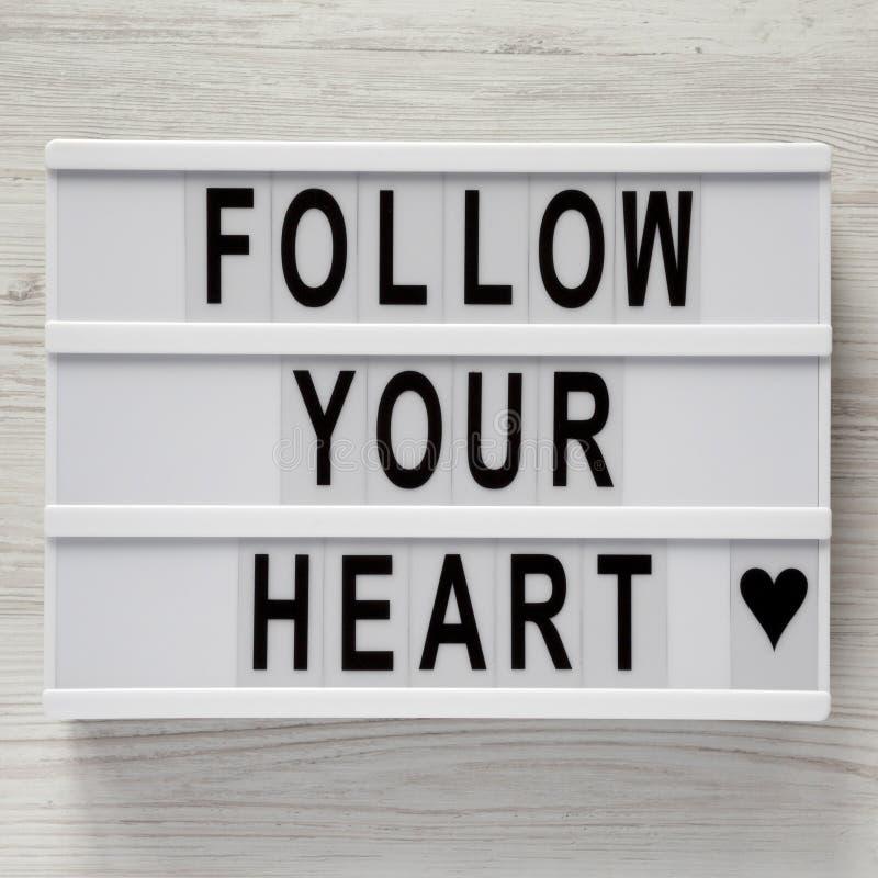 Lightbox mit Text 'folgen Ihrem Herzen 'auf einem weißen hölzernen Hintergrund, Draufsicht Flache Lage, obenliegend Valentinsgruß stockfotografie