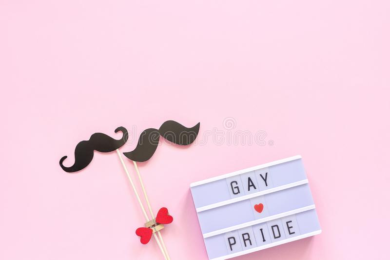 Lightbox text Gay pride and couple paper mustache props on pink background. Concept Homosexuality gay love National Day. Against Homophobia or International Gay royalty free stock photography