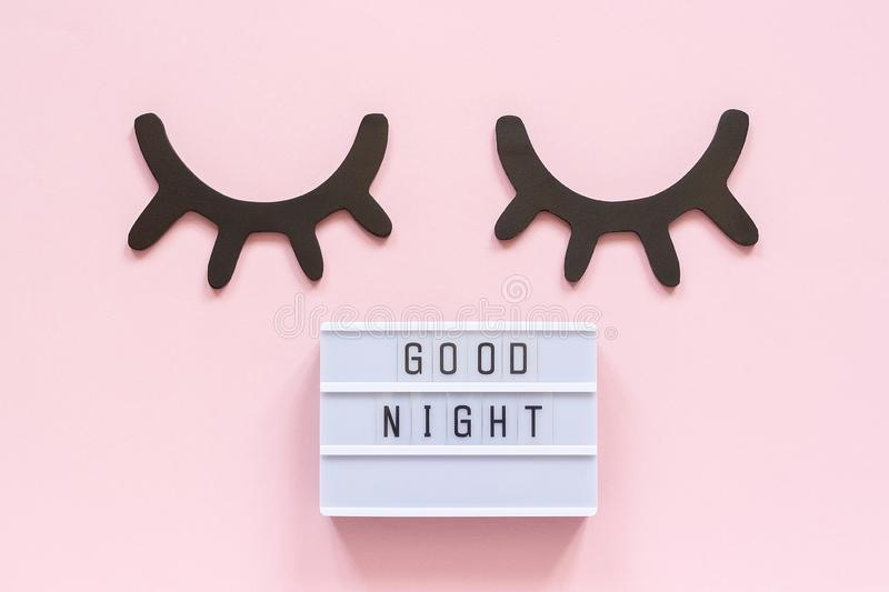 Lightbox text Good Night and decorative wooden black eyelashes, closed eyes on pink paper background. Concept Sweet. Dreams Greeting card Top view Creative flat stock photo
