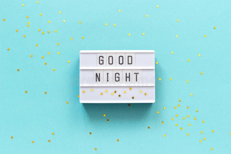 Lightbox text Good Night and gold star on blue paper background. Concept Sweet dreams Greeting card Top view Creative flat lay.  royalty free stock photo
