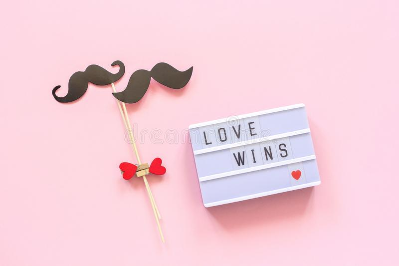 Lightbox with text Love wins and couple paper mustache props on pink background. Concept Homosexuality gay love. National Day Against Homophobia or royalty free stock image