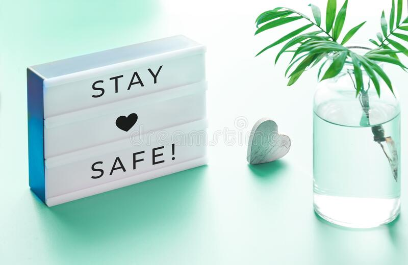 Lightbox with text. `Stay safe`, glass bottle with palm leaf and wooden heart. Wishing well to friends and family during quarantine and social distancing due to royalty free stock photography
