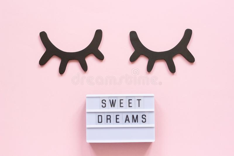 Lightbox text Sweet dreams and decorative wooden black eyelashes, closed eyes on pink paper background. Concept Good. Night Greeting card Top view Creative flat stock images
