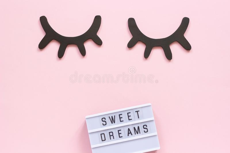 Lightbox text Sweet dreams and decorative wooden black eyelashes, closed eyes on pink paper background. Concept Good night. Greeting card Top view Creative flat stock photo