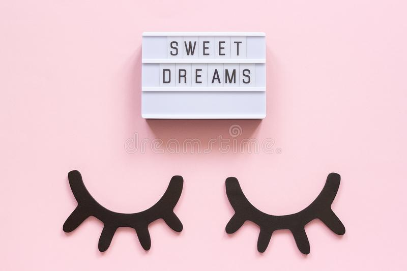 Lightbox text Sweet dreams and decorative wooden black eyelashes, closed eyes on pink paper background. Concept Good night. Greeting card Top view Creative flat royalty free stock photo
