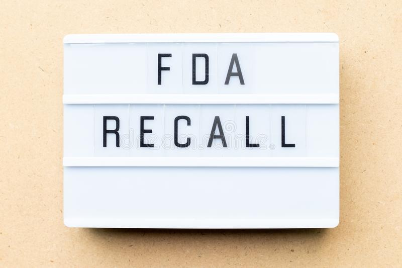 Lightbox with word fda recall on wood background. White lightbox with word fda recall on wood background royalty free stock photo