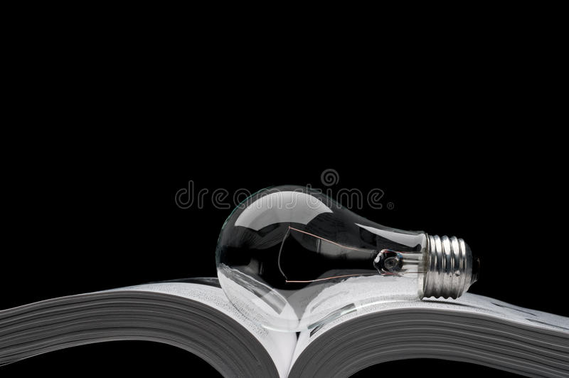 Lightbulb on a book showing ideas from inspiration royalty free stock photography