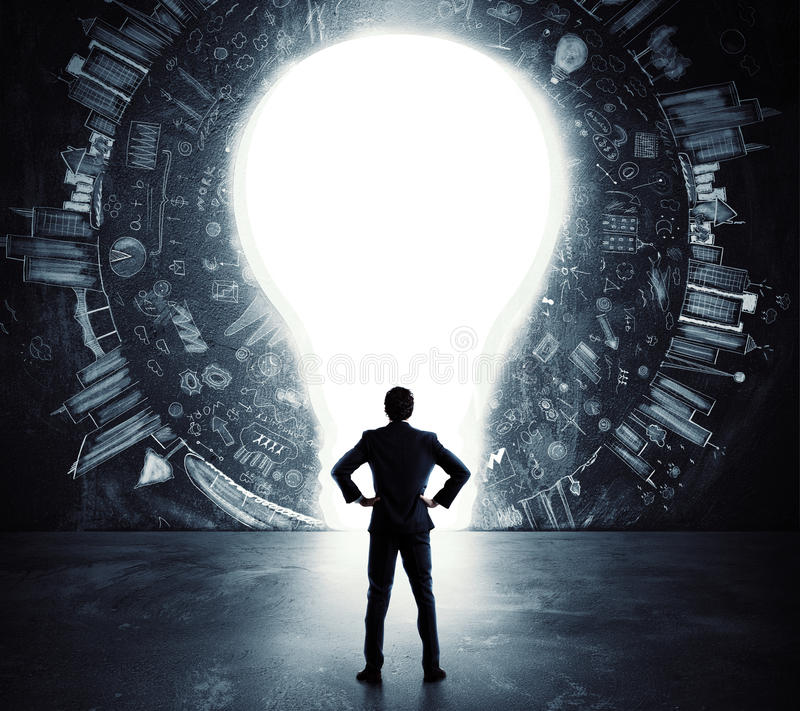 Lightbulb door. Businessman looks at a big hole in the shape of a light bulb on the wall royalty free stock images