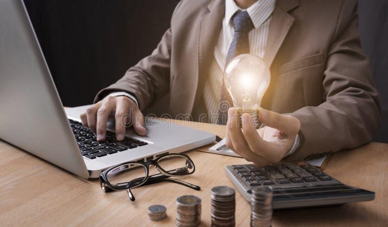 lightbulb för hand för affärsman hållande med att använda räknemaskinen arkivfoton
