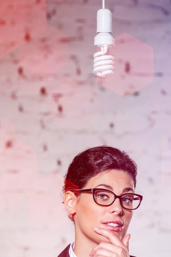 Lightbulb het hangen over jonge nadenkende onderneemster tegen bakstenen muur op kantoor royalty-vrije stock afbeelding