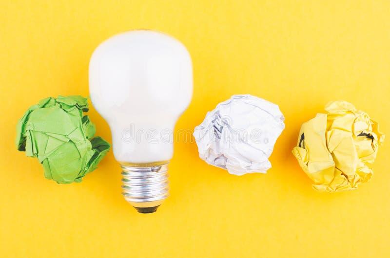 Lightbulb i miie papier na żółtym tle obrazy stock