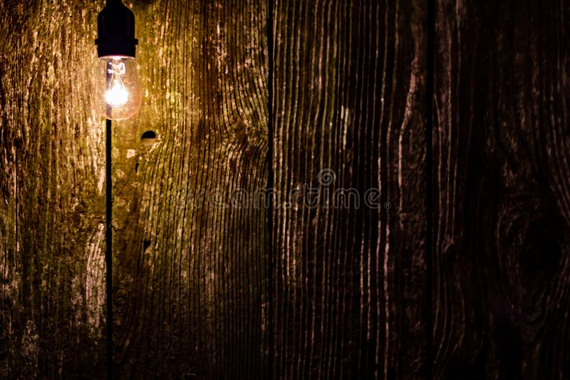 Lightbulb on an old rustic fence at night with space for text stock photos