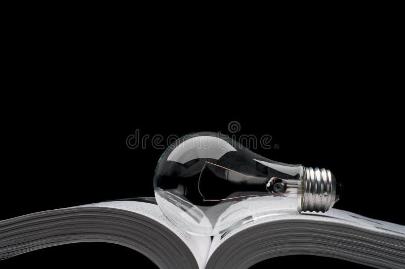 Lightbulb op een boek dat ideeën van inspiratie toont royalty-vrije stock fotografie