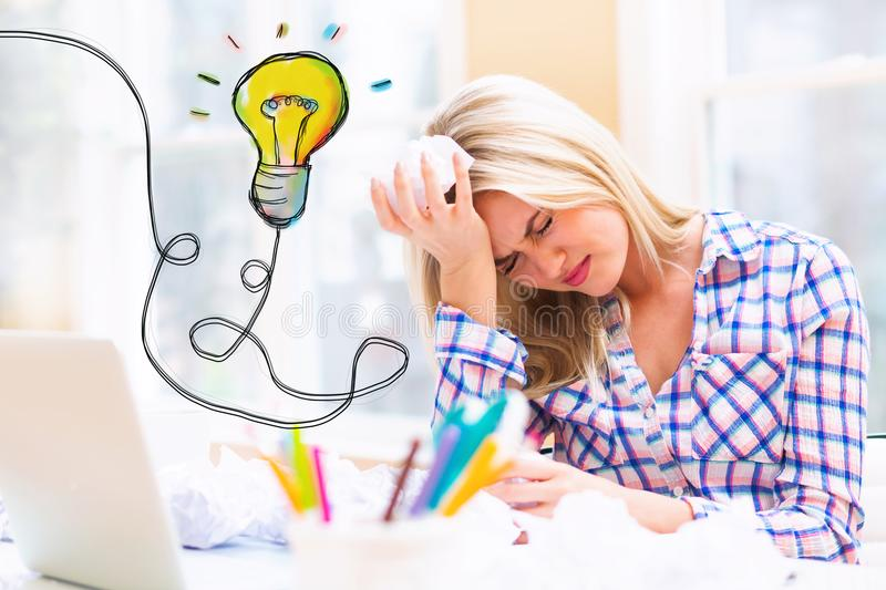 Lightbulb with woman with crumpled paper balls. Lightbulb with young woman with crumpled paper balls stock image