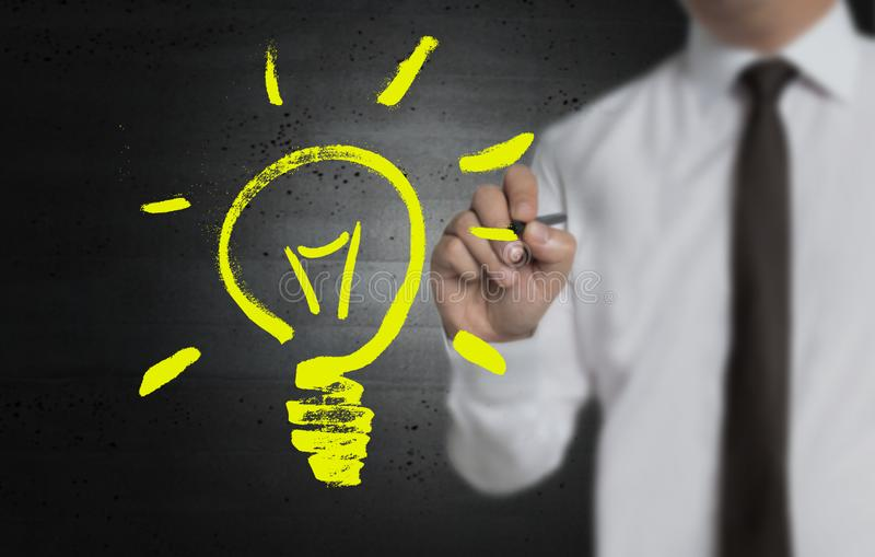 Lightbulben målas av affärsmannen på skärmen royaltyfri bild