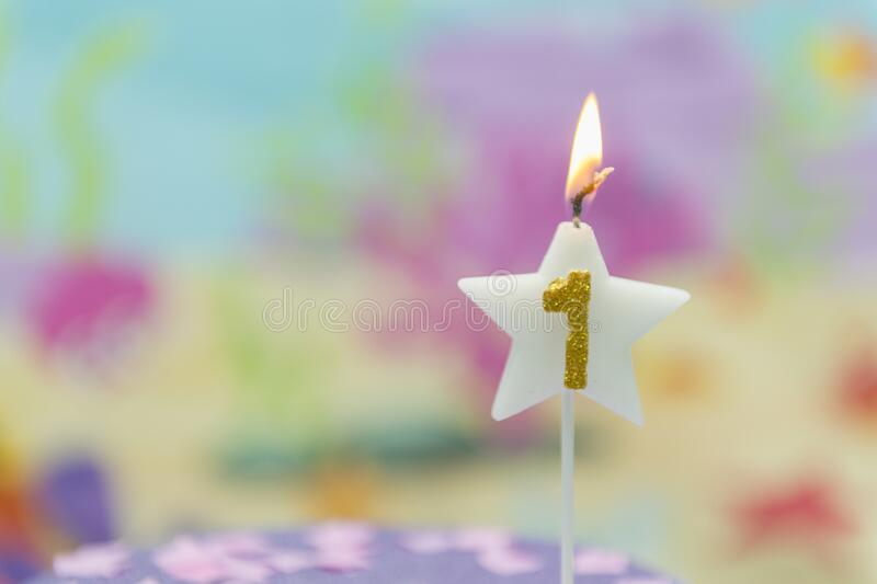 Lighted birthday candle in star shape with blurred background. 1 year anniversary, deep sea theme. Celebration, party and joy royalty free stock images