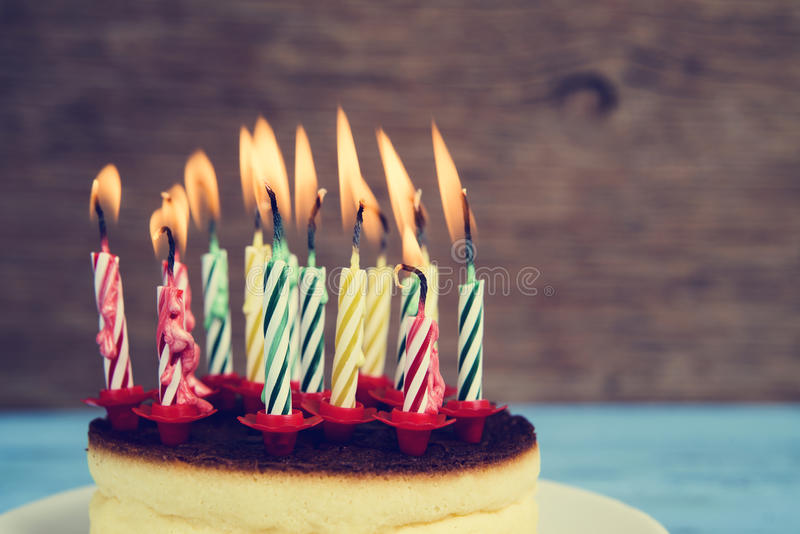 Lighted birthday candles on a cheesecake, with a retro effect. Closeup of a cheesecake with some lighted birthday candles of different colors, with a retro stock image