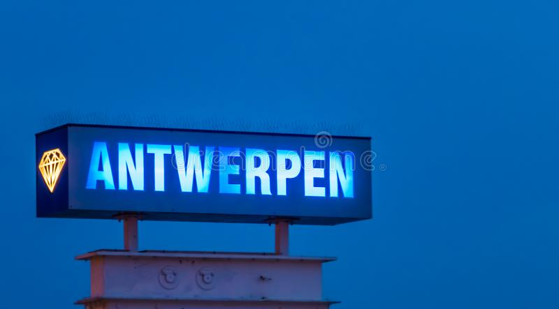 Lighted blue neon light board with the text Antwerpen, Sign post illuminated by night in antwerp, Belgium. A lighted blue neon light board with the text stock photo