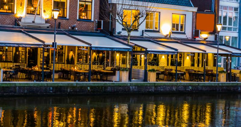 Lighted buildings with terraces at night, beautiful water scenery in the city of Alphen aan den Rijn, The netherlands. Lighted buildings with terraces at night royalty free stock image