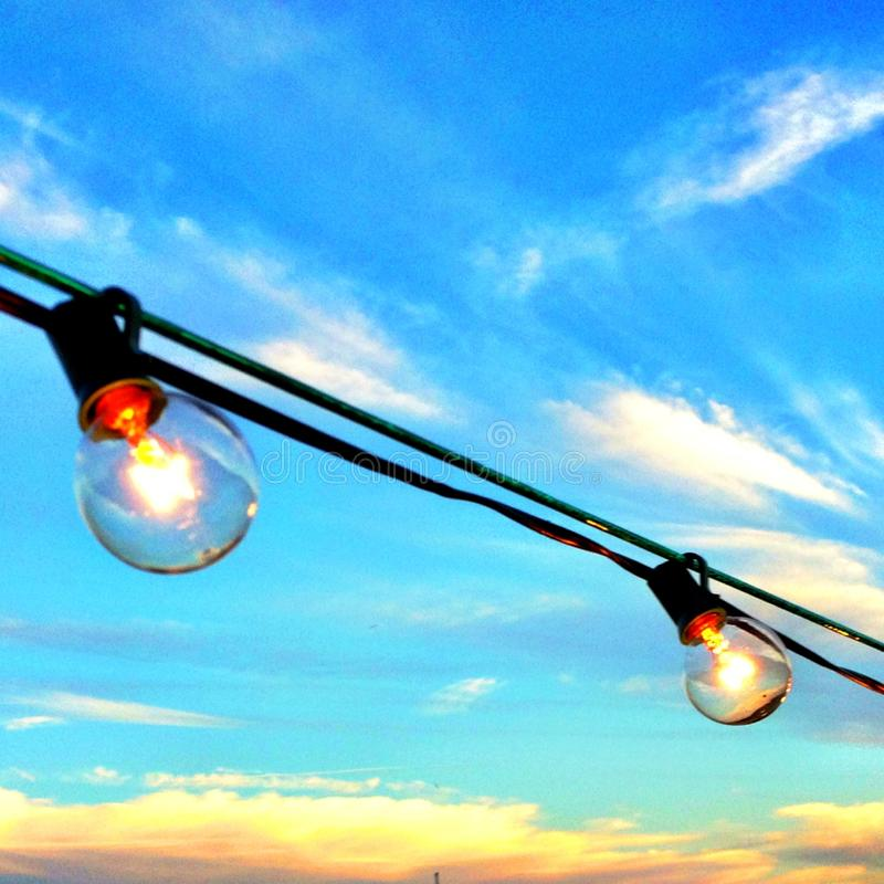 Lighted bulbs hanging outdoors in daylight