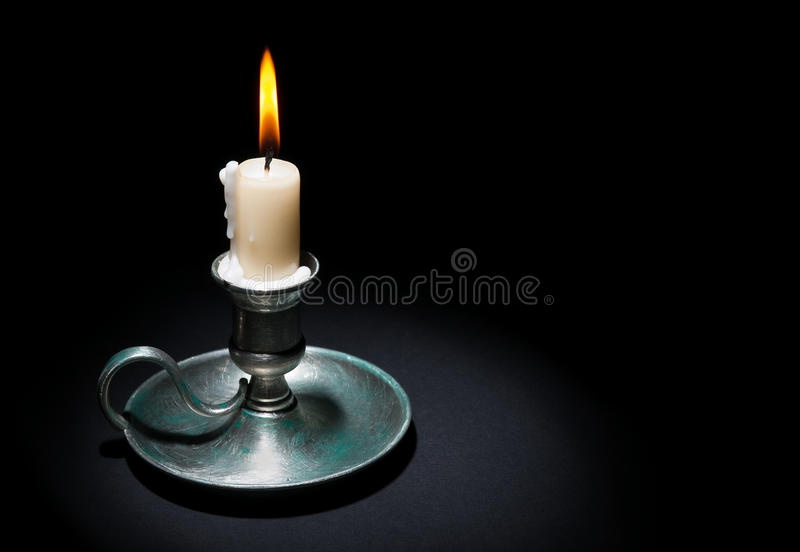 Lighted Candle. In an old tin candlestick on a black background stock photo